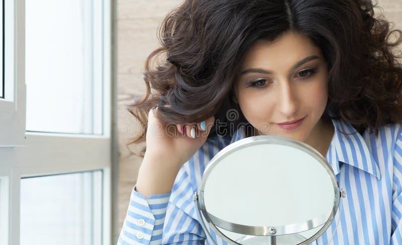 Reflexión del peinado del cliente femenino en espejo Concepto de moda y de belleza Morenita hermosa con el borrachín imagen de archivo