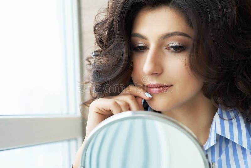 Reflexión del peinado del cliente femenino en espejo Concepto de moda y de belleza Morenita hermosa con el borrachín fotos de archivo libres de regalías