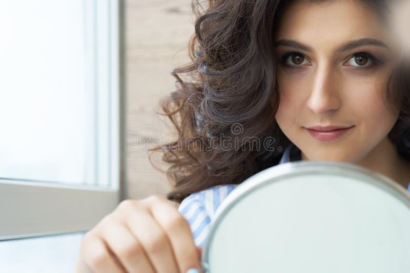 Reflexión del peinado del cliente femenino en espejo Concepto de moda y de belleza Morenita hermosa con el borrachín fotos de archivo