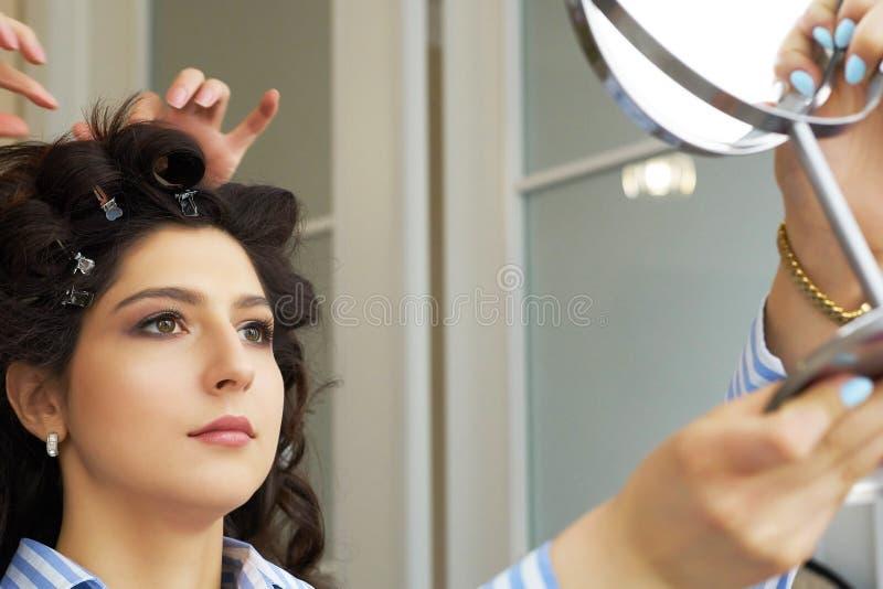 Reflexión del peinado del cliente femenino en espejo Concepto de moda y de belleza Morenita hermosa con el borrachín fotografía de archivo libre de regalías