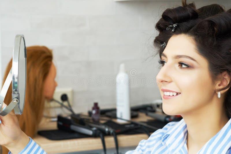 Reflexión del peinado del cliente femenino en espejo Concepto de moda y de belleza Morenita hermosa con el borrachín imagenes de archivo
