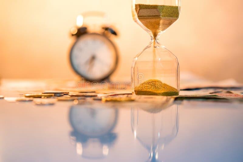 Reflexión del reloj de arena con moneda en la tabla foto de archivo
