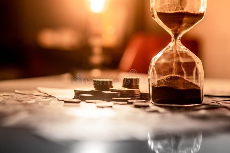 Reflexión del reloj de arena con moneda en la tabla que brilla intensamente foto de archivo