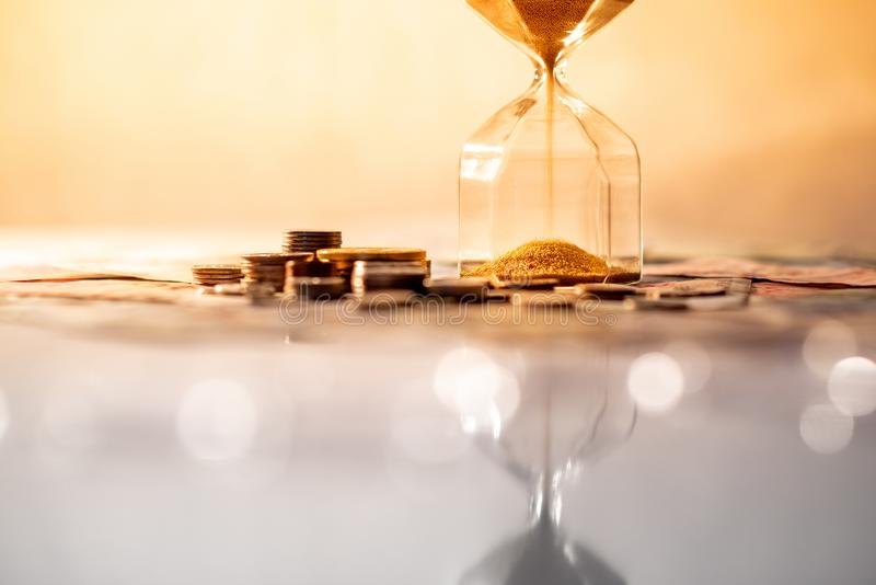 Reflexión del reloj de arena con moneda en la tabla que brilla intensamente fotos de archivo libres de regalías