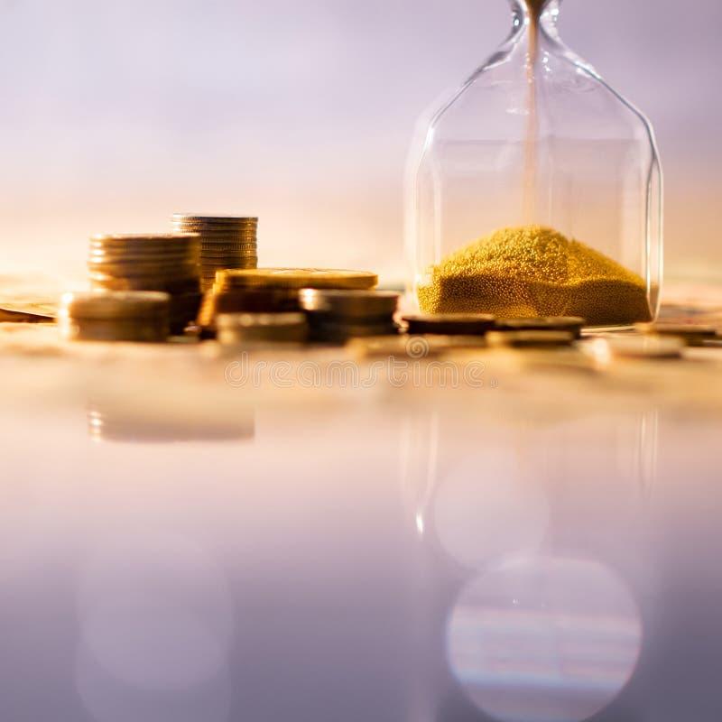 Reflexión del reloj de arena con moneda en la tabla que brilla intensamente imagen de archivo