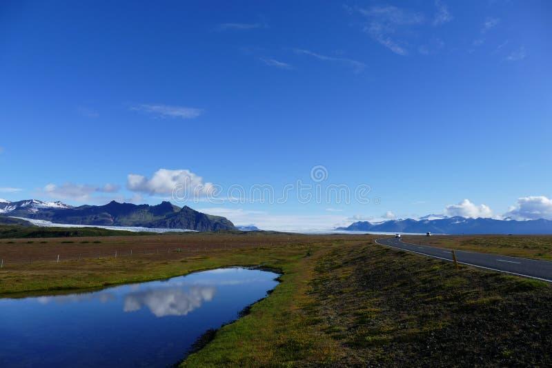 Reflexión en un lago al lado de la carretera de circunvalación en un día soleado glorioso, Islandia fotos de archivo