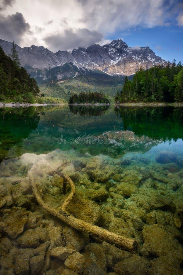 Reflexión hermosa del pico de la montaña más alta Zugspitze en el lago y las nubes tempestuosas que sorprenden, Baviera, Alemania fotografía de archivo