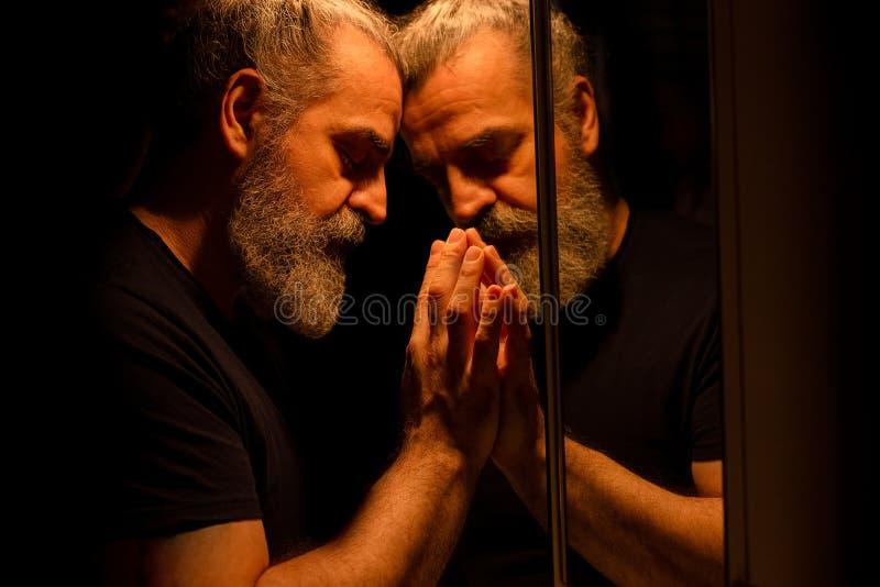 Reflexi?n del hombre barbudo en una oscuridad, llevando a cabo su cabeza con sus manos con la expresi?n dolorosa imagen de archivo libre de regalías