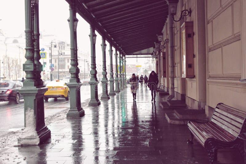 Reflexion av arkitektur, folk på våt trottoar royaltyfri fotografi