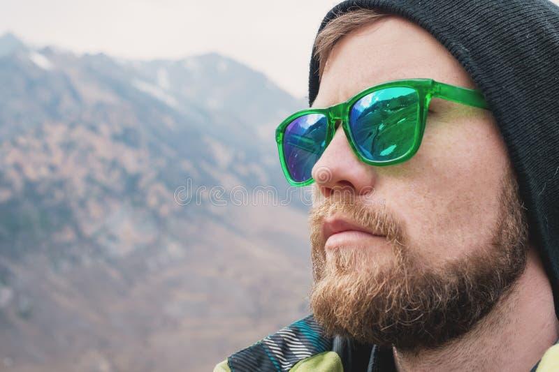 Reflexion av bergen i solspegelexponeringsglasen av en hipster, en stor stående fotografering för bildbyråer