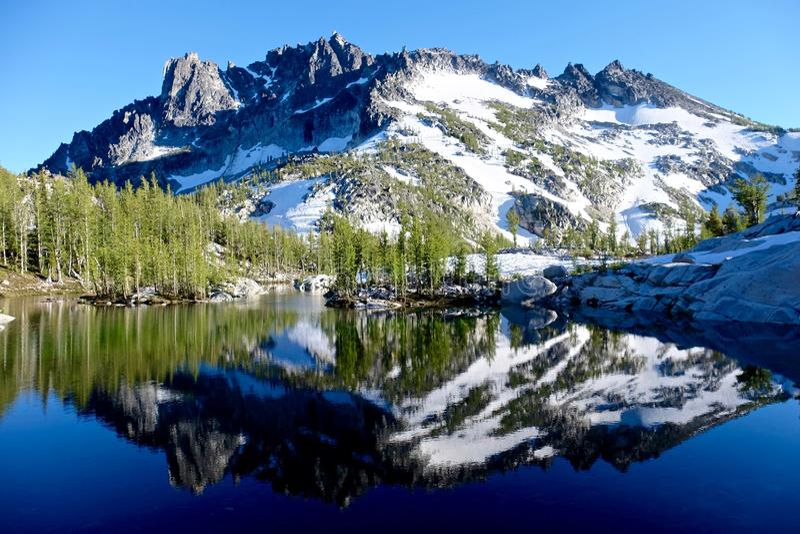 Reflexion av berget i den alpina sjön royaltyfria bilder