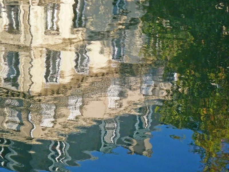 Reflexion av byggnad och träd i vatten arkivfoto