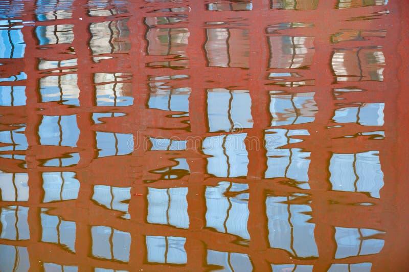 Reflexion av byggnadsfönstren i den förhållandevis lugna floden royaltyfri foto