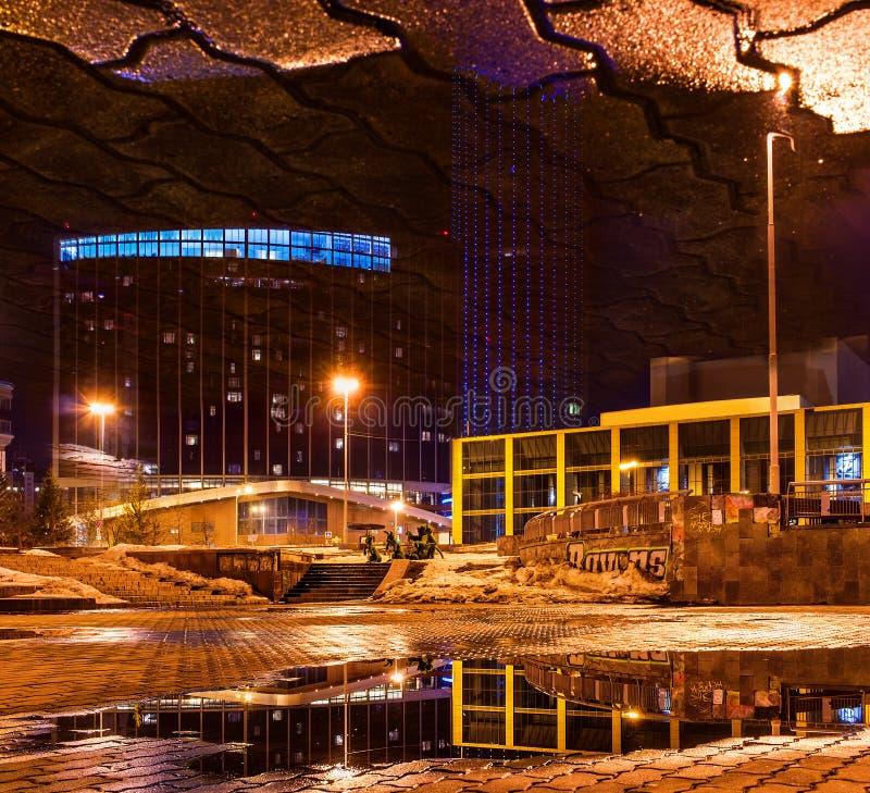 Reflexion av den centrala delen av staden av Yekaterinburg i pölarna på trottoartegelplattan royaltyfri foto