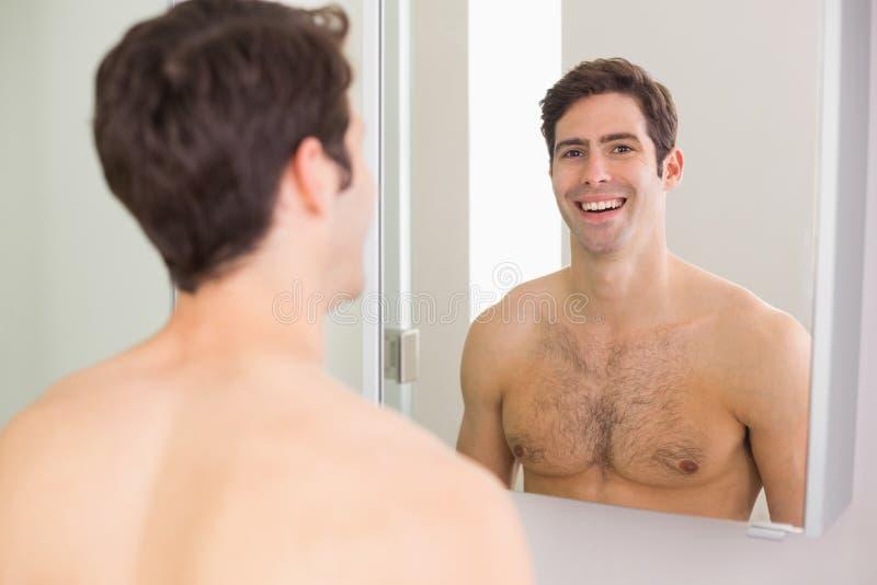Reflexion av den shirtless mannen som ler i badrum royaltyfria foton
