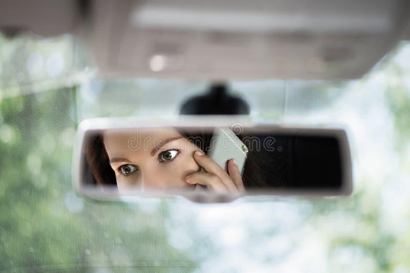 Reflexion av den unga kvinnan som talar på en mobiltelefon i spegeln för bakre sikt för bil Ingen mobiltelefon, medan k?ra arkivfoto