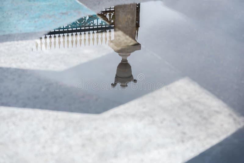Reflexion av det dekorativa historiska metallstaketet i pöl efter regn Mystiskt abstrakt begrepp, portingång i drömmar royaltyfria bilder