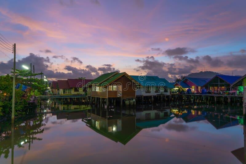 Reflexion av det thailändska traditionella asiatiska fiskeläget Sväva hus på solnedgångbakgrund i landsbygd, Phuket stad thailand royaltyfri foto