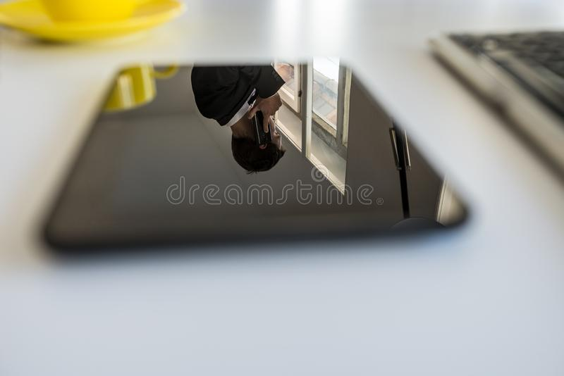 Reflexion av en affärsman som talar på en telefon i en digital minnestavla fotografering för bildbyråer