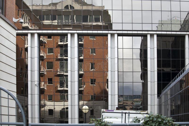 Reflexion av en affärsmitt i en glasvägg av en byggnad i London arkivbilder