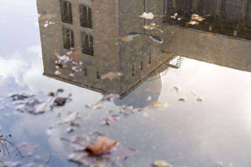 Reflexion av en byggnad i en pöl arkivbilder