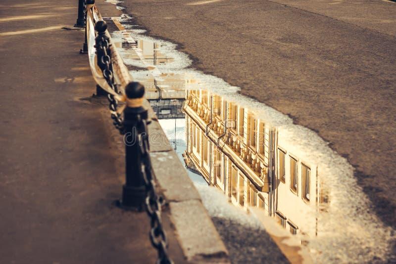 Reflexion av en byggnad i en pöl, ett metallstaket, poler med en kedja arkivfoton