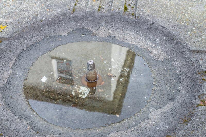 Reflexion av en byggnad i vattenpölen av en vattenutmatare, Tyskland arkivfoton