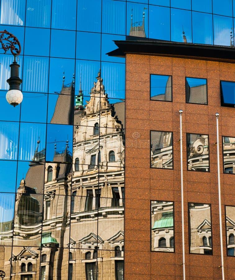 Reflexion av en gammal byggnad i ny glass byggnad Kontra modernt för gammal arkitektur reflekterat i exponeringsglas Stad av Libe royaltyfria bilder