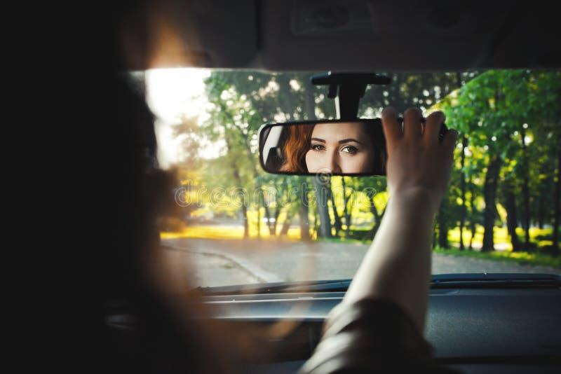 Reflexion av en gladlynt härlig flicka i en spegel av en bil arkivbilder
