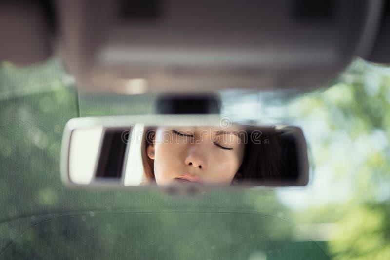 Reflexion av en härlig ung kvinna som kopplar av med stängda ögon i spegeln för bakre sikt för bil fotografering för bildbyråer