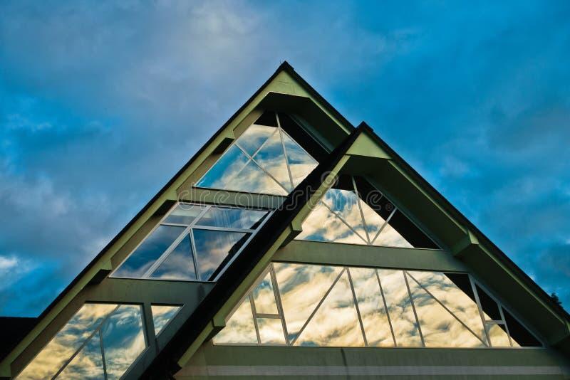 Reflexion av en himmel i en glass form för triangel på en byggnad på Bled royaltyfri foto