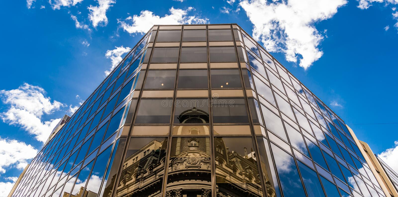 Reflexion av en kyrka på en exponeringsglasbyggnad i Buenos Aires på den Reconquista gatan arkivfoto