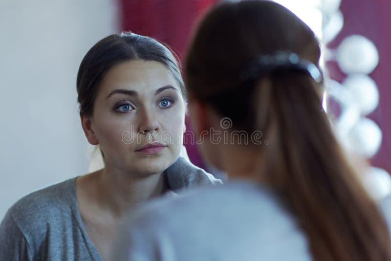 Reflexion av en ung attraktiv caucasian kvinna som ser in i en spegel Bära tillfälliga härliga blåa ögon, allvarlig blick royaltyfria bilder