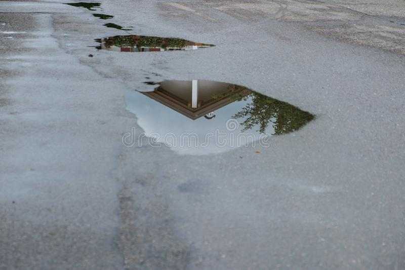Reflexion av ett hus i en vattenpöl efter en regnstorm fotografering för bildbyråer