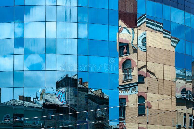 Reflexion av forntida byggnader på exponeringsglasfasaden av en modern byggnad arkivfoto