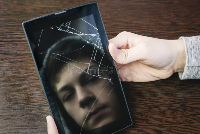 Reflexion av framsidan av tonåringen i skärmen av den brutna minnestavlan Tonårs- ensamhet, fördjupning royaltyfri fotografi