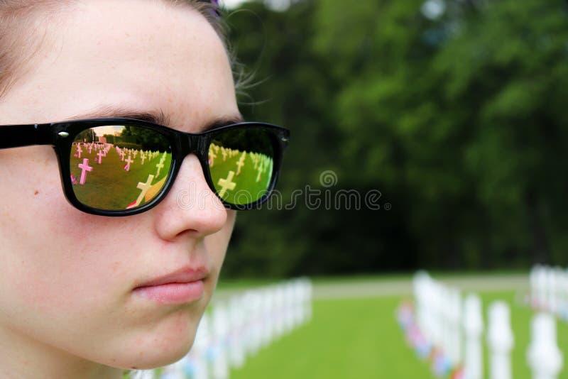 Reflexion av gravar och flaggor i en tonårs- flickas solglasögon arkivbild