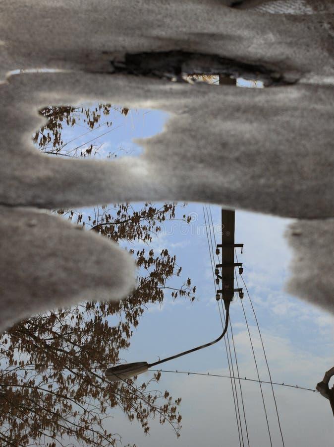 Reflexion av himlen, konturn av en gatalampa och ett träd i en pöl på dålig asfalt fotografering för bildbyråer