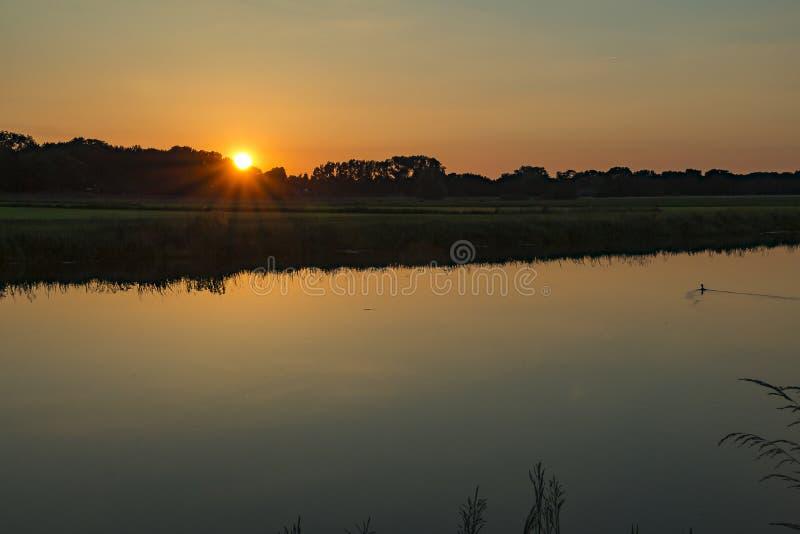 Reflexion av himlen och inställningssolen längs floden Vecht royaltyfri foto