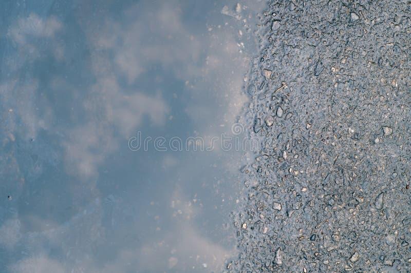 Reflexion av himmel på den våta gatan royaltyfria bilder