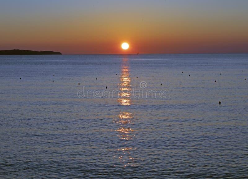 Reflexion av inställningssolen på havsyttersida royaltyfria bilder