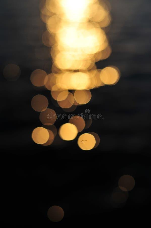 reflexion av ljus på vattenyttersida i solnedgång arkivbilder