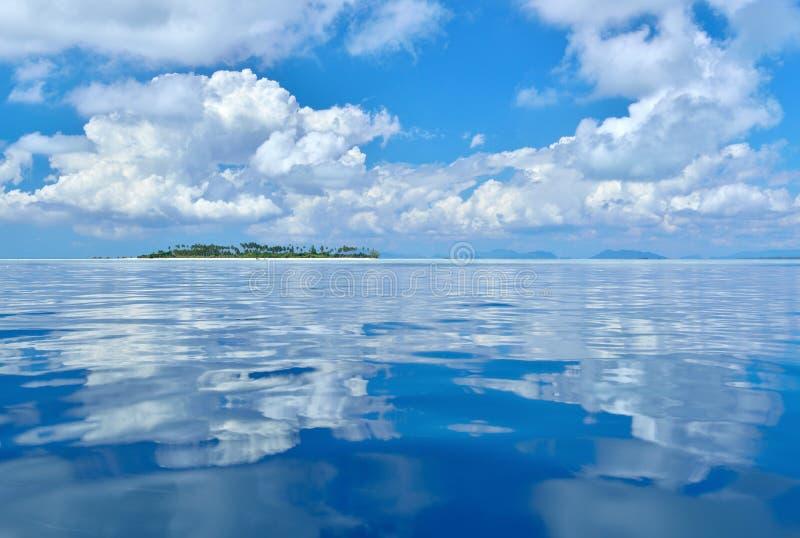 Reflexion av moln på det lugna och stillsamma havet royaltyfria foton