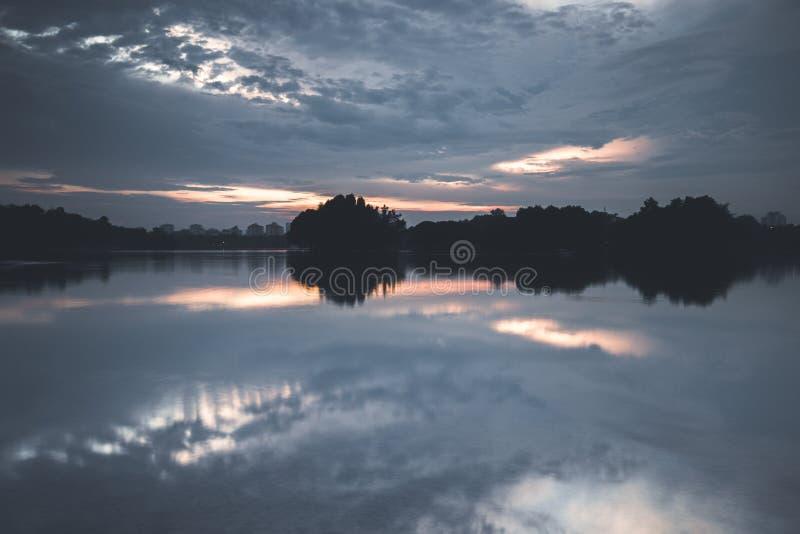 Reflexion av moln under solnedgång Skottet på sjön i ett fritids- parkerar royaltyfri foto