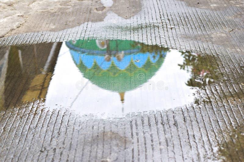 Reflexion av moskékupolen i dammet efter hällregn royaltyfri fotografi