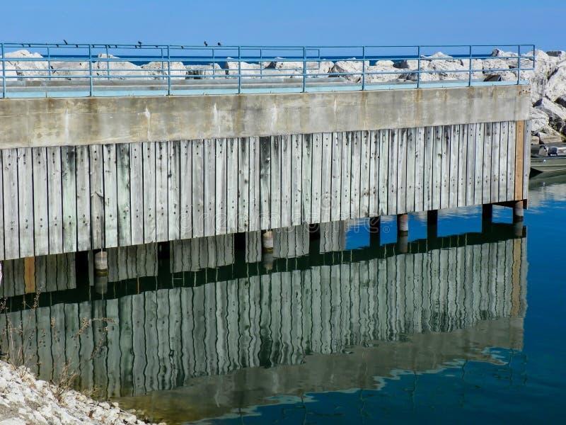 Reflexion av pir på den Lake Michigan hamnen royaltyfri bild