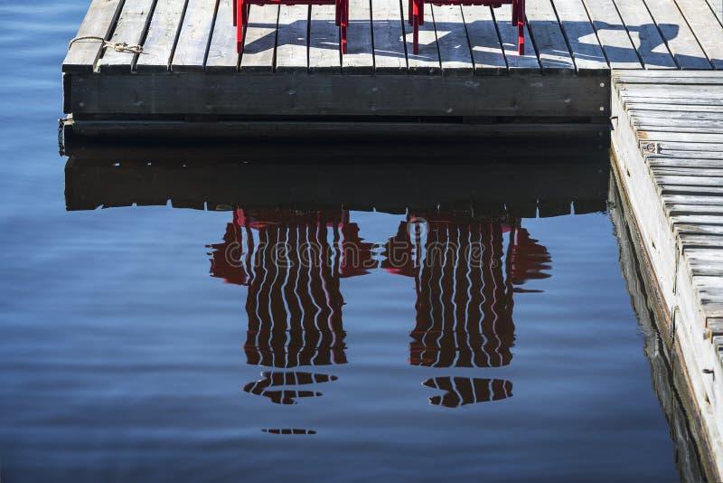 Reflexion av röda stolar på skeppsdocka royaltyfri foto