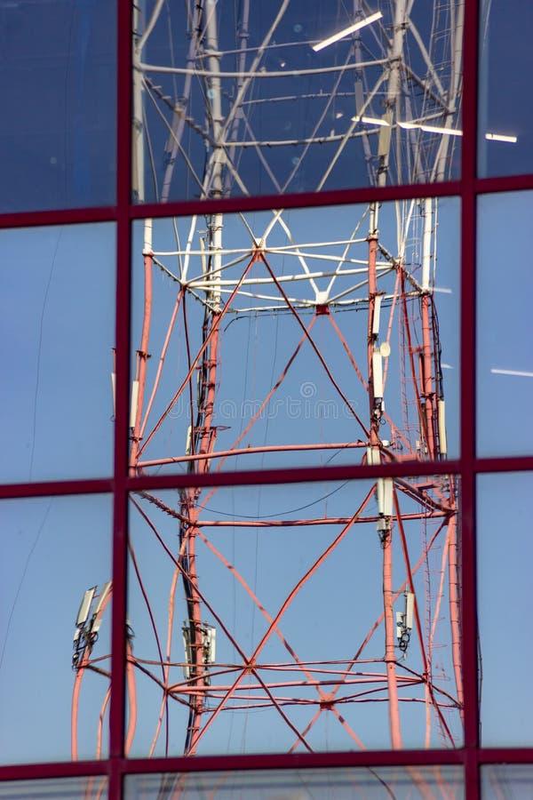 Reflexion av radiosändningtornet med cell- kommunikationsantenner i spegelfönster av byggnad Mobil internet arkivbild