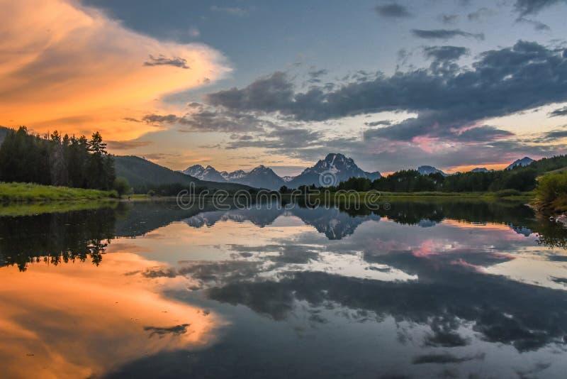 Reflexion av storslagna Tetons i Jackson Lake på solnedgången med härliga moln royaltyfri foto