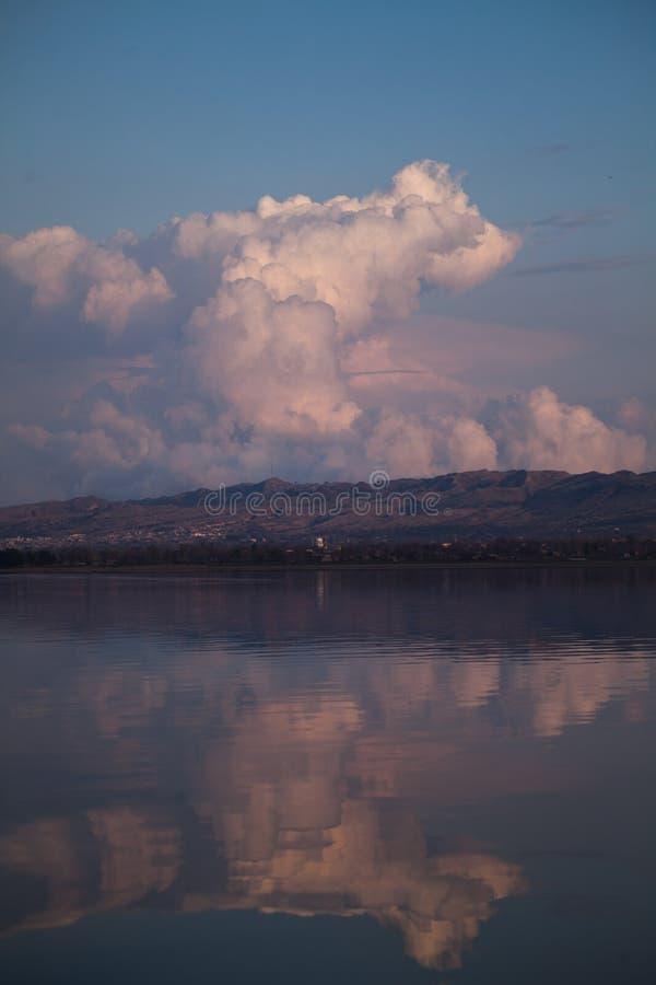 Reflexion av träd och hus på solnedgången fotografering för bildbyråer